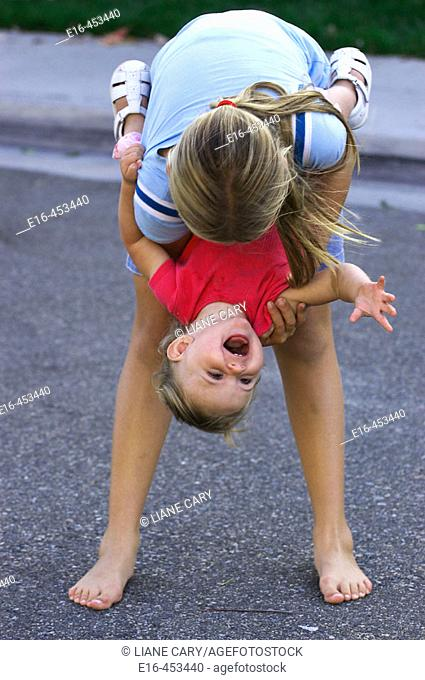 Girl holding laughing toddler upside down