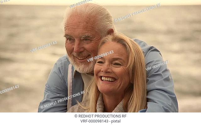 Mature couple sitting on beach