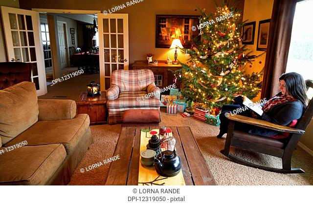 A woman reads a Bible in her rocking chair beside a Christmas tree in her home; Chilliwack, British Columbia, Canada
