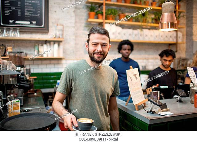 Portrait of male barista serving coffee in cafe