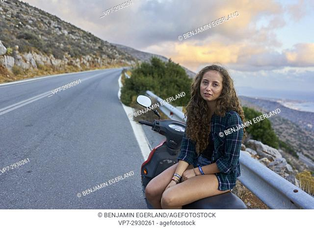 young girl sitting on moped during morning sunrise during travel adventure, near Heraklion, Crete, Greece