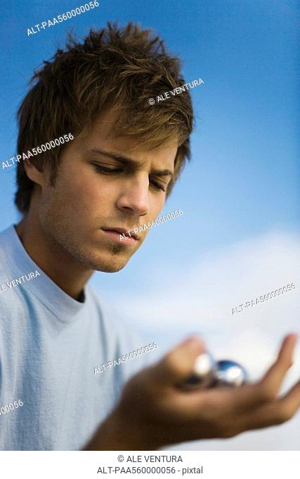Young man looking at yin yang balls with furrowed brow