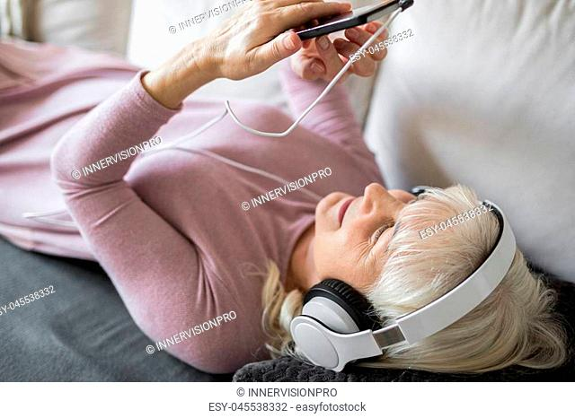 Portrait of glad senior lady lying on couch listening music on mobile