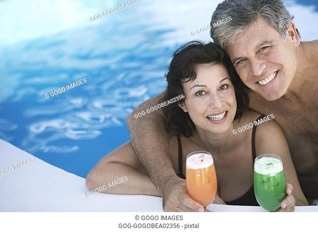 Couple having tropical drinks in pool