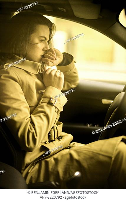 confident woman sitting in car at driver's side, wearing coat, thoughtful determined, pensive reminiscing emotion, in Munich, Germany