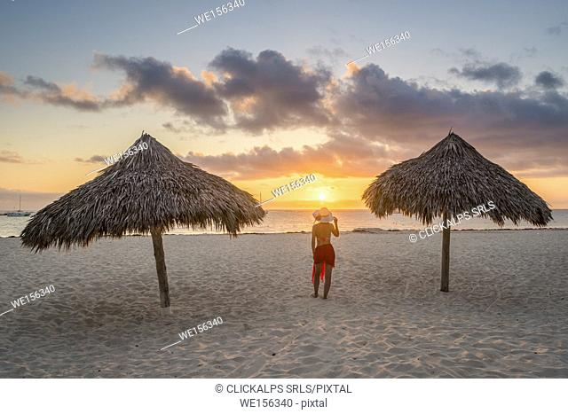 Bavaro Beach, Bavaro, Higuey, Punta Cana, Dominican Republic. Woman by thatch umbrellas on the beach at sunrise (MR)