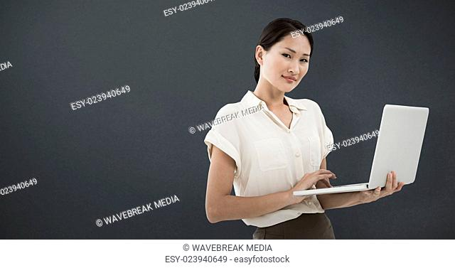 Composite image of asian businesswoman using laptop
