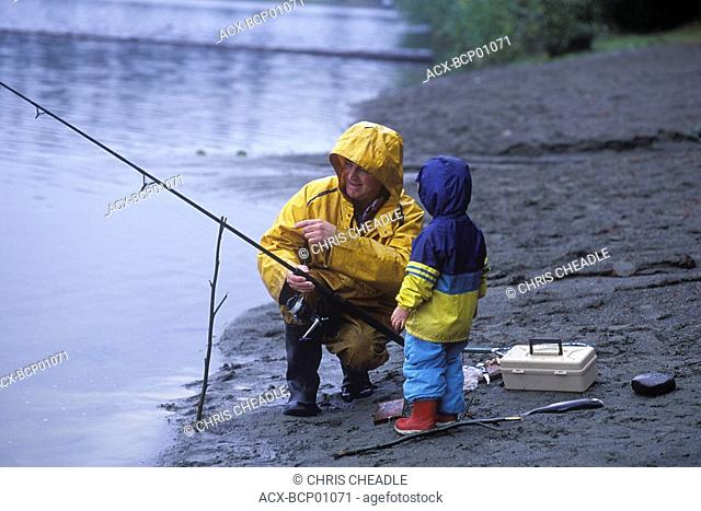Grandfather and boy fish trout at lake side, Vancouver Island, British Columbia, Canada