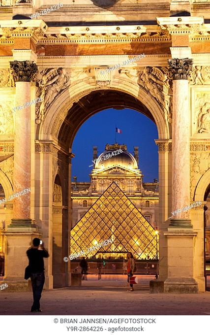Tourists taking photo of Musee du Louvre viewed through the archway of Arc de Triomphe du Carrousel, Paris France