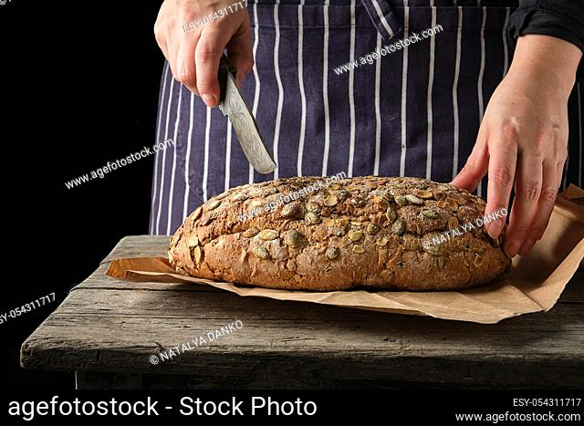 woman in an blue apron with a knife in her hand about to cut round baked bread on a wooden table, dark background