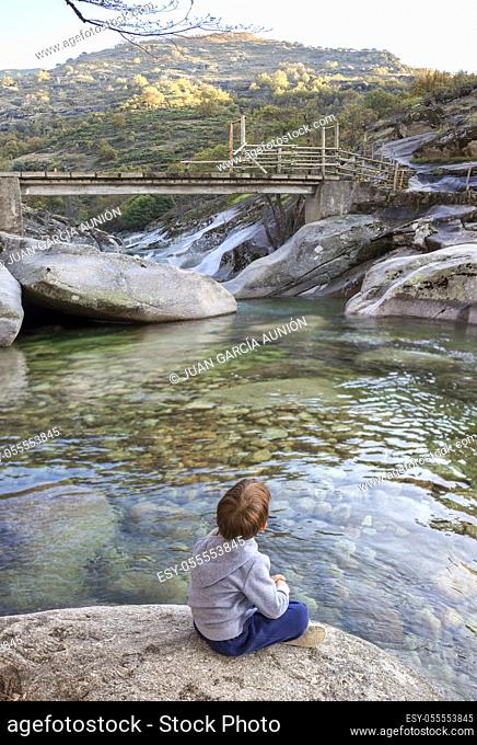 Little boy sitting at riverside of Los Pilones Gorge at Natural Reserve Garganta de los Infiernos. Outstanding place for enjoying nature in Extremadura, Spain