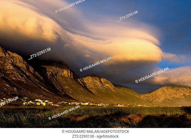 Landscape photo of a dramatic lenticular cloud sunset over the mountains of Bettys Bay. Bettys Bay, Western Cape, South Africa