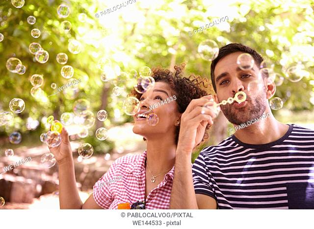 Two young friends joyfully blowing bubbles and smiling in the dappled afternoon sunshine with some trees around them wearing casual clothing