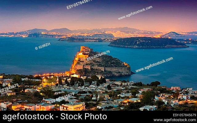 Sunset view of Gulf of Naples and Ischia Island with Aragonese Castle or Castello Aragonese. On horizon there are Procida Island