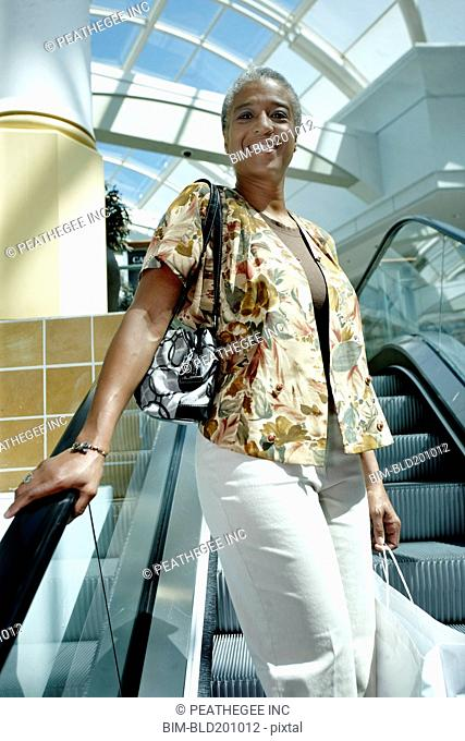 Black woman on mall escalator