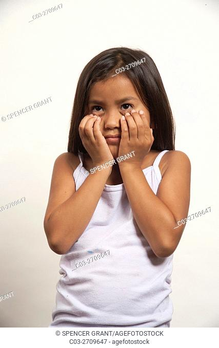 A demonstrative Native American girl member of the Acjachemen tribe covers her face in shyness. . MODEL RELEASE