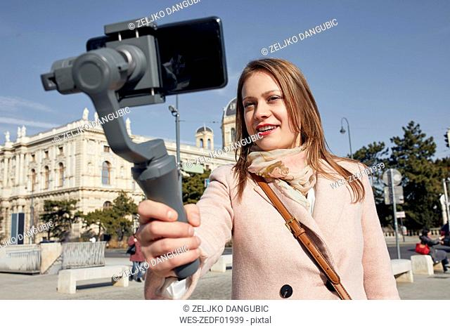 Austria, Vienna, portrait of smiling young woman using selfie-stick for taking photo with smartphone