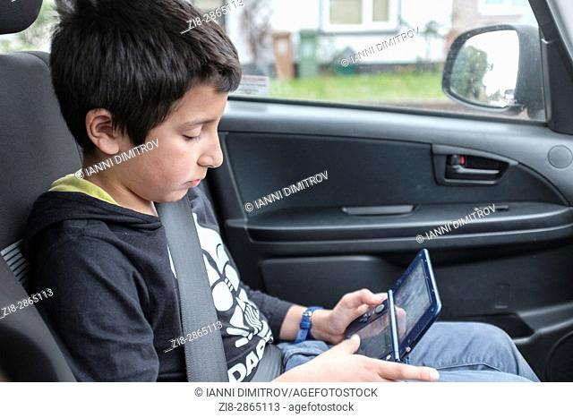 Boy,10 years old, plays computer game in car,UK