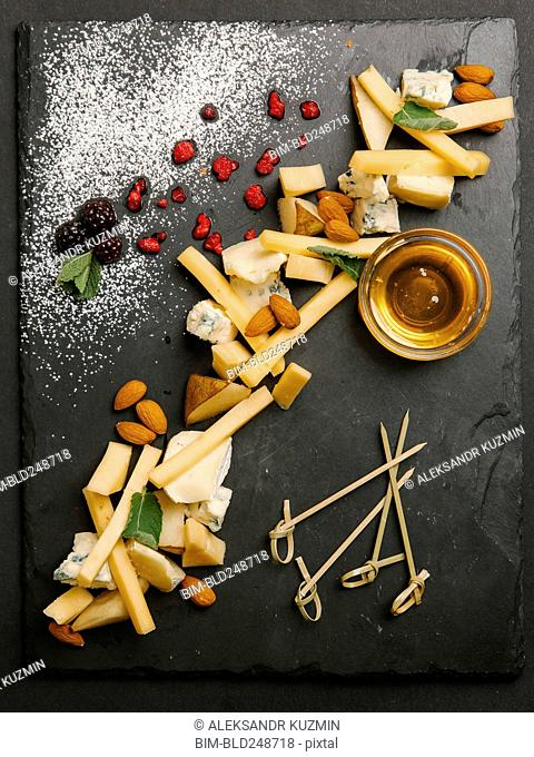 Cheese and nuts with honey on slate