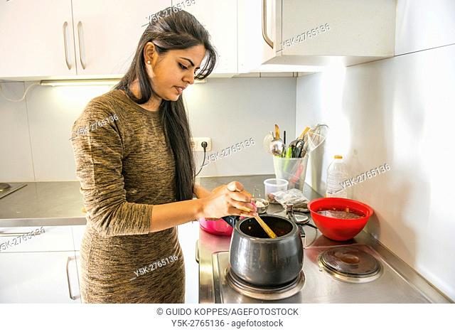 Aachen, Germany. Young, female Indian exchange student to Aachen university preparing a hot lunch inside her dormatory kitchen