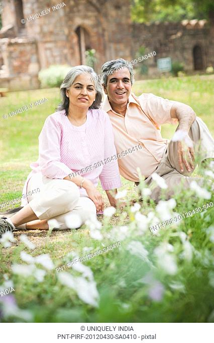 Mature couple sitting back to back on grass in a park, Lodi Gardens, New Delhi, India
