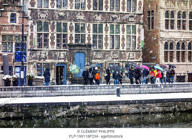 Guided tour with tourists visiting the city Ghent during snow shower in winter, East Flanders, Belgium