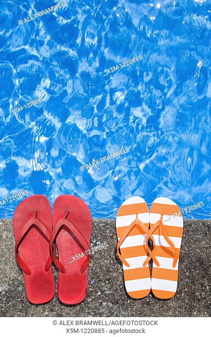 Two pairs of flip flops or thongs by a sparkling blue swimming pool