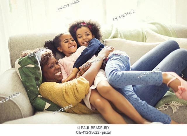 Playful mother and daughters cuddling on sofa