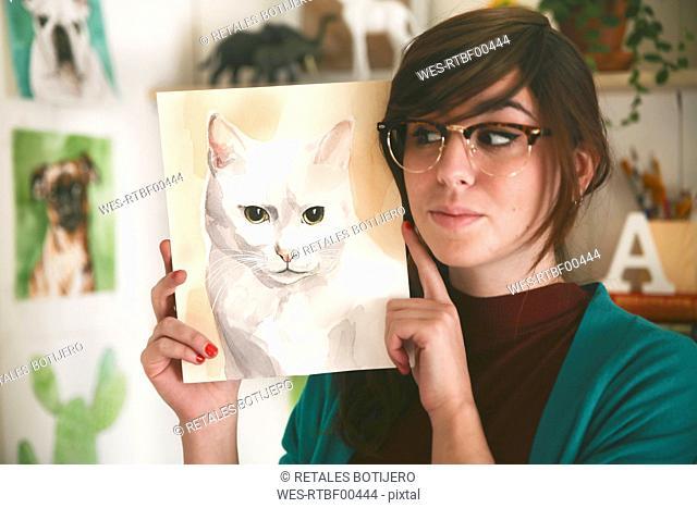 Portrait of artist showing aquarelle of a cat