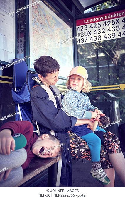 Mother with children at bus stop