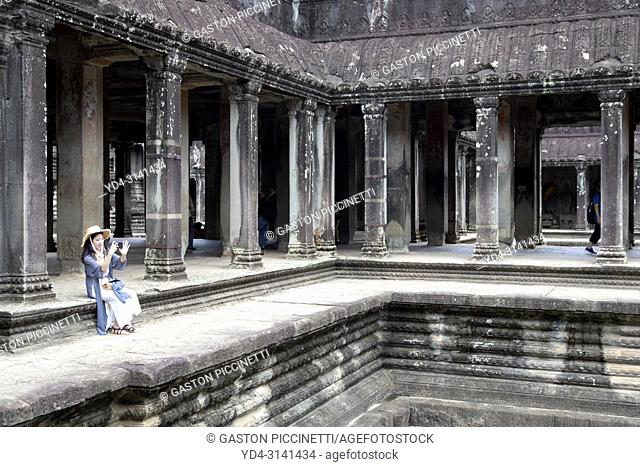 Tourist taking pictures in Angkor Wat Temple, Angkor Temple Complex, Siem Reap Province, Cambodia, Asia, UNESCO. It was originally constructed as a Hindu temple...