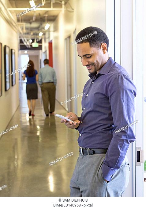 Black businessman using cell phone in office hallway