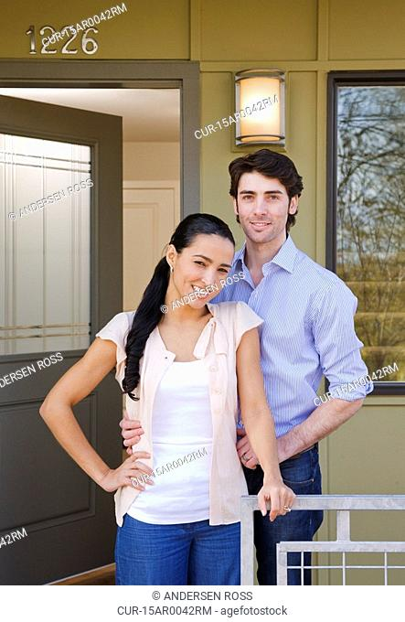 couple on front porch with sold sign