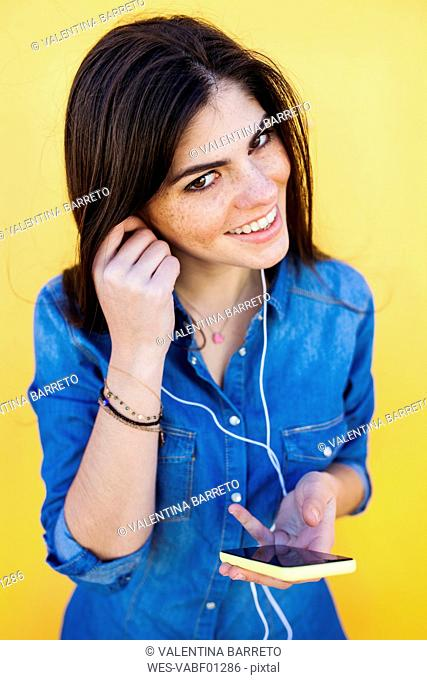 Portrait of smiling young woman with earphones and smartphone in front of yellow background