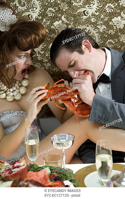 Portrait of couple indulging in lobster at elegant dinner party