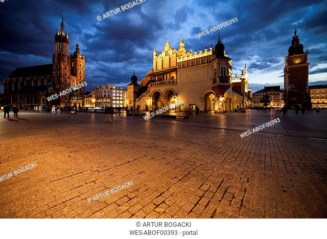 Poland, Krakow, Main Square in the Old Town at evening twilight with St Mary's Church, Cloth Hall and Town Hall Tower