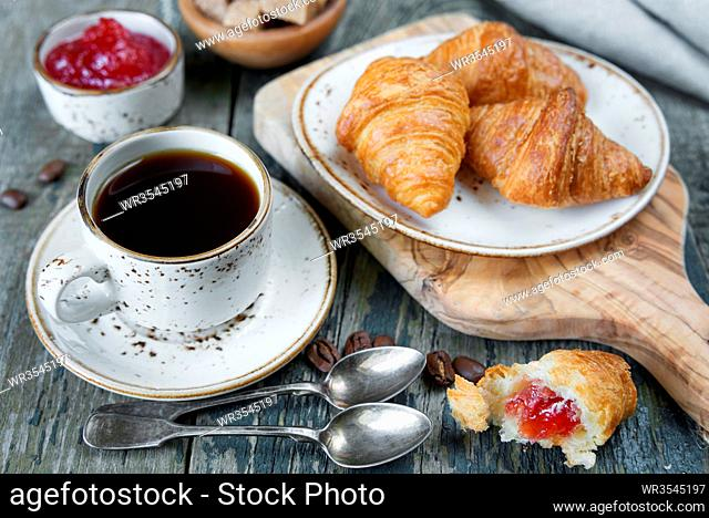Light breakfast consisting of a cup of black coffee and croissants with a stuffing from raspberry jam