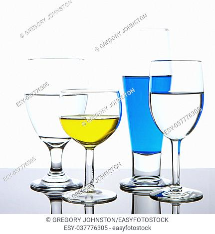 Various glasses that are filled with colored liquid for an abstract look