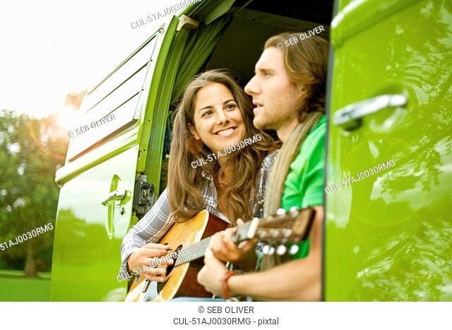 Couple playing guitar in van