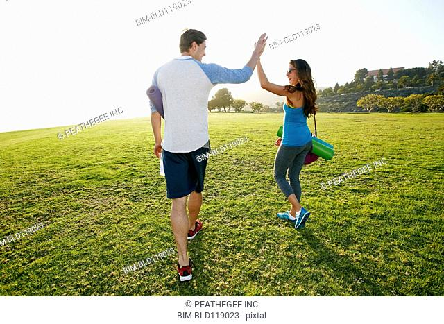 Couple high fiving in park