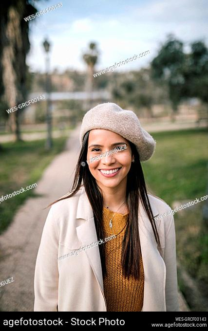 Portrait of smiling young woman with beret in a park