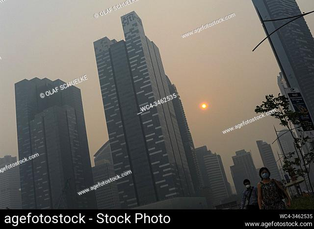 Singapore, Republic of Singapore, Asia - People wearing face masks walk through the hazardous haze that shrouds the central business district with its...