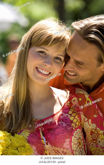 Couple hugging and smiling outdoors