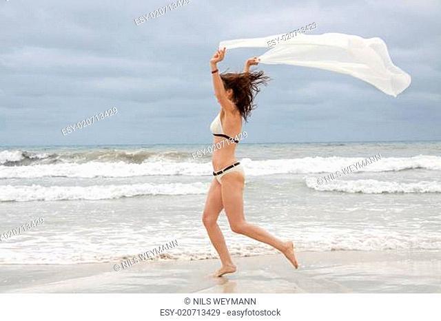 attraktive erwachsene frau sorgenfrei weisses tuch am strand