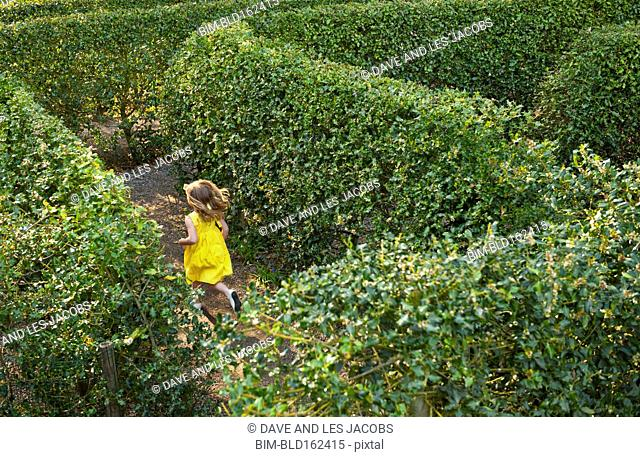 Caucasian girl running in hedge maze