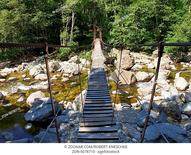 Hängebrücke über Fluss in den italienischen Alpen im Vale Grande