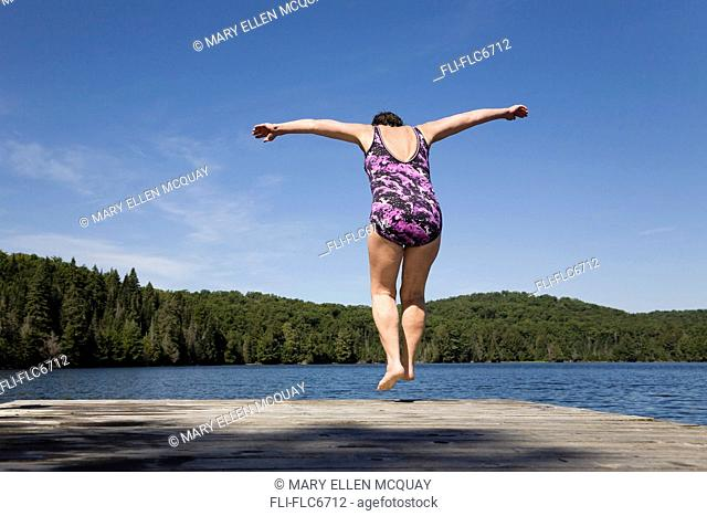 Woman lifting off a cottage dock to dive into a lake, Algonquin Park, Ontario, Canada