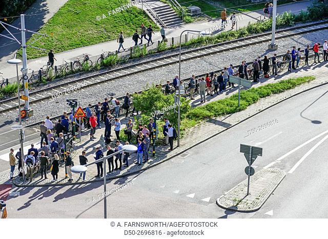 Morning well-organised queue line for commuter bus, street scene, Stockholm, Sweden