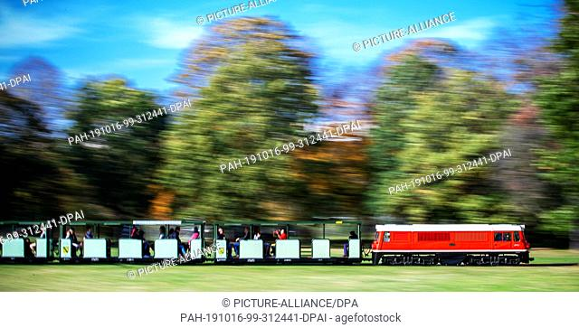 15 October 2019, Saxony, Dresden: The locomotive EA01 of the Dresdner Parkeisenbahn pulls a passenger train through the already autumnally colourful Great...
