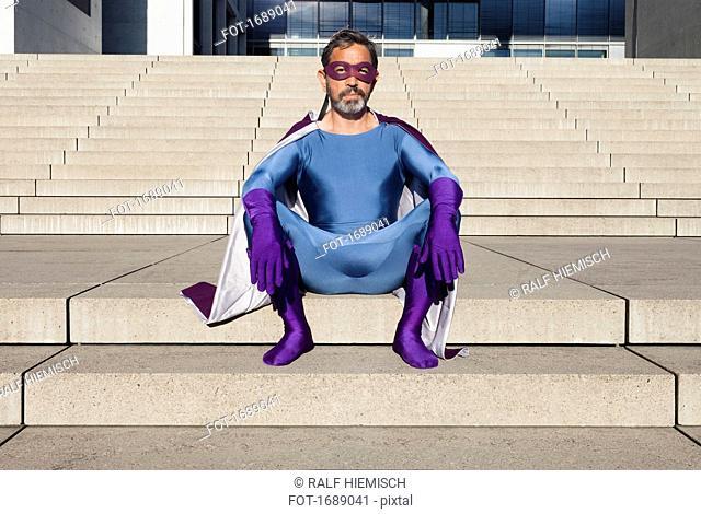 Portrait of man dressed as superhero sitting on steps